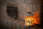 White lantern on a shelf near the fireplace against a brick wall — Stock Photo