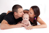 Happy family kiss - mother, father and baby — Stock Photo