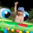 Baby boy and kids rubber pool — Stock Photo #27699561