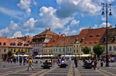 SIBIU, ROMANIA - JUNE 08, 2014: Tourists visit main square in Sibiu, Romania. Sibiu was designated a European Capital of Culture for the year 2007 — Stock Photo