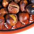 Roasted chestnuts in red clay dish — Stock Photo
