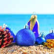 Photo: Christmas blue baubles and cones on sand in seashore