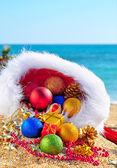 Palline di Natale e scatole regalo con il cappello di Natale sulla sabbia — Foto Stock