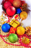 Christmas baubles and gift boxes in the christmas hat on the sand — Stock Photo