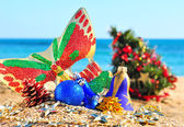 Christmas baubles, face mask, christmas tree in the beach — Stock Photo
