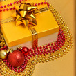 Yellow gift box with christmas baubles and beads around — Stock Photo #14395599
