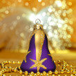Stock Photo: Christmas purple bell with beads around on golden light backgrou