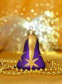 Fialová vánoční zvon s korálky kolem na zlaté světlo poz — Stock fotografie
