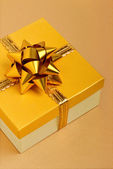 Golden gift box on the beige tablecloth — Stock Photo
