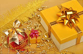Golden gift boxes, christmas bauble, plume, garland — Stock Photo