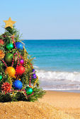 Christmas tree on the sand in the beach — Stock Photo