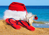 Santa Claus hat and slippers on the seashore against blue sky — Foto Stock