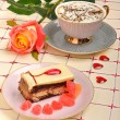 Cup of coffee, rose and cake on tablecloth — Stock Photo #19956651