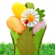 Easter colored cloth eggs, an ox-eye daisy in the flowerbed — Stock Photo