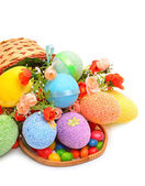 Easter colored plastic eggs, flowers and caramels in the basket — Stock Photo