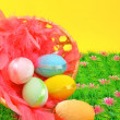 Basket with easter eggs on the green grass — Stock Photo