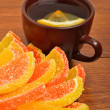 Ceramic brown cup with tea and candied fruit on the brown board — Stock Photo