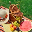 Beach hat, sun glasses, picnic basket with fruits and  bottle of — Stock Photo