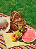 Stranden hatt, solglasögon, picknickkorg med frukter och flaska — Stockfoto