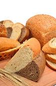 Pão fresco, espigas de trigo e fatias de pão na placa de madeira — Fotografia Stock