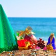 Christmas baubles, gift box and cone on the sand in the seashore — Stock Photo
