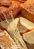 Fresh bread, wheat ears, wheat grains on the wooden background — Stock Photo