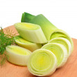 Fresh sliced leeks and dill on a wooden board — Stock Photo