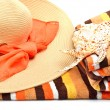Woman beach hat, bright towel and a seashel — Stock Photo
