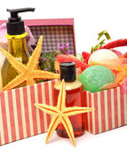 Gel bottles, bath bomnbs with starfishes in gift boxes — Stock Photo