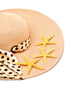 Woman beach hat and a seashell  — Stock Photo
