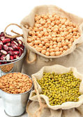 Chick-pea, mung beans, kidney-beans in the sacks isolated on white — Stock Photo