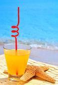 морские звезды, стакан апельсинового коктейля на фоне голубого моря — Стоковое фото