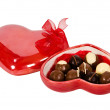 Chocolate candies in heart shaped box with red ribbon — Stock Photo