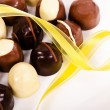 Assortment of dark and white chocolate candies with yellow ribbon — Stock Photo