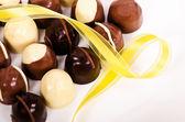 Assortimento di caramelle di cioccolato scuri e bianchi con nastro giallo — Foto Stock