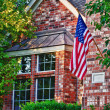 House with patriotic American flag — Stock Photo #21842009