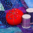 Stock Photo: Quilt pattern with quilting thread and pincushion