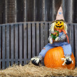 Scarecrow on a pumpkin and hay — Stock Photo