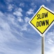 Slow Down yellow road sign — Stock Photo