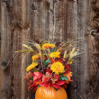 Pumpkin flower arrangement on hay — Stock Photo #33909583