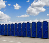 A row of blue portable toilets — Photo