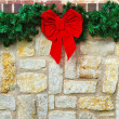 Red Christmas bow on stone fence — Stock Photo