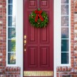 Christmas wreath on a red door — Stock Photo #36312925