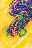 Colorful Mardi Gras beads against yellow — Stock Photo
