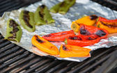 Grilling colorful peppers on foil — Stock Photo