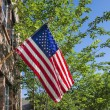 American flag in front of a brick home — Stock Photo