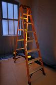 Escalera de tijera se encuentra cerca de una ventana — Foto de Stock