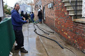 Pumping water out of building basement in the Sheapsheadbay neighborhood due to flooding from Hurricane Sandy in Brooklyn, New York — Stock Photo