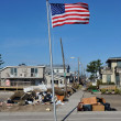 Stock Photo: NEW YORK, NY - NOVEMBER 09: Americflag flies from front yard of house in damaged areNovember 9, 2012 in Breezy Point part of Far Rockaway in Queens borough of NY.