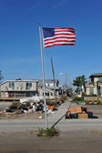 NEW YORK, NY - NOVEMBER 09: An American flag flies from the front yard of a house in a damaged area November 9, 2012 in the Breezy Point part of Far Rockaway in the Queens borough of NY. — Stock Photo